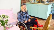 Magdalena Truchan sits in a wheelchair. She has blonde hair and wears a checked hat, colourful jacket and bright red knee-high boots, which match her lipstick . Her legs are crosed.